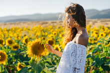 Side View Of Thoughtful Ethnic Female Touching Flower Standing In Booming Sunflower Field And Looking Away