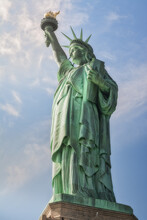 Statue Of Liberty Located On Liberty Island In New York Against Blue Cloudy Sky
