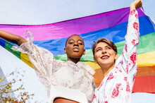 From Below Of Multiethnic Lesbian Couple Standing With Rainbow LGBT Flag In Raised Hands In City
