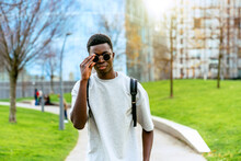 Young African American Man Wearing A T-shirt And Sunglasses On A Path Between Lawns In The City.