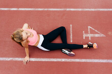 From Above Blonde Young Sportswoman Sitting On The Floor Resting On Tracking Field