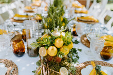 Long Table Served With Glassware And Plates And Decorated With Lemon Compositions With Plants