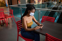 Portrait Of Attractive Young Afro Latin Woman Wearing A Facemask And Using Smartphone In A Commercial Mall, Colombia