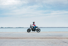 Side View Of Unrecognizable Female Biker In Stylish Clothes And Helmet Riding Motorcycle On Empty Asphalt Road Near Sea Against Cloudy Blue Sky