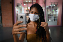 Portrait Of Attractive Young Afro Latin Woman Wearing A Facemask Takes Selfie With Smartphone In A Commercial Mall, Colombia