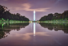 Obelisk Washington Monument Reflected In Water Surrounded By Beautiful Green Park During The Evening