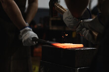 Crop Anonymous Craftsmen In Gloves Making Hot Metal Detail With Hammer In Blacksmith Workshop