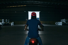 Back View Of Unrecognizable Male Biker In Casual Clothes And Cap Riding Modern Motorcycle In Spacious Industrial Hangar With Pile Of Metal Sheet Coils