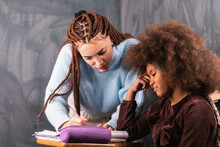 Cheerful African American Pupil And Teacher Doing Task Together At Table During Lesson In Classroom With Chalkboard