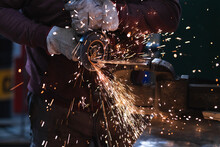 Crop Anonymous Master In Gloves Processing Iron Product With Spark Grinder Clamped In Vice In Forge