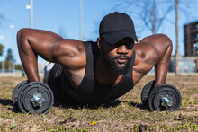 Ground Level Of Young Muscular Black Male Athlete In Sportswear Exercising With Dumbbells On Lawn In City