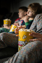Cropped Young Amazed Siblings Kids Sitting Comfortable On Sofa With Popcorn Bucket While Eating And Watching TV