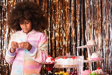 Charming African American Girl With Afro Hairstyle Standing With Donut In Room With Various Sweets On Background Of Golden Tinsel Stripes