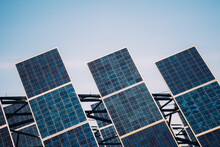 Modern Solar Panels Installed In Field Against Cloudy Sky In Photovoltaic Power Station