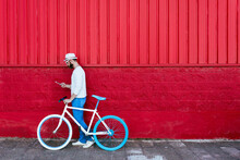 Full Body Side View Of Trendy Bearded Male In Stylish Outfit And Sunglasses Walking On Red Wall Using Mobile Phone On Street With Modern Bicycle