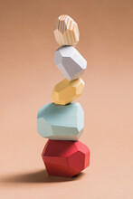Wooden Blocks In Shapes Of Gems Of Various Colors Stacked On Beige Background In Studio