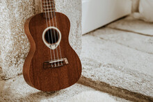 Close-up Of A Ukulele Leaning Against A White Wall
