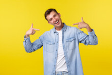 Portrait Of Happy Handsome Blond Male Student Pointing At Himself And Smiling Joyfully. Guy Show-off, Bragging Over Personal Achievement, Being Excited As Got Job Or Promotion, Yellow Background