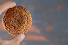 Holding Crispy Oatmeal Cookie Between Two Fingers