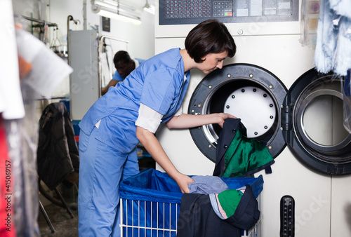Fotografia, Obraz Female worker of dry cleaning loading laundry washing machine with dirty clothes