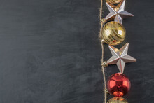 Colorful Ornaments Hanged From The Rustic Thread On The Dark Stone Background