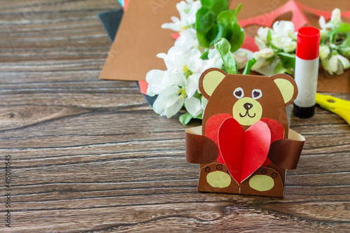 Mother's Day greeting card gift - teddy bear with a heart on a wooden table. Childrens creativity project, handmade, crafts for kids. Copy space.