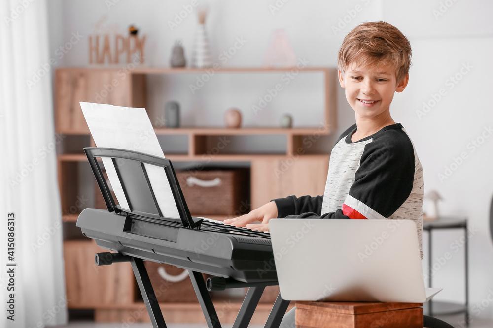 Fototapeta Little boy taking music lessons online at home