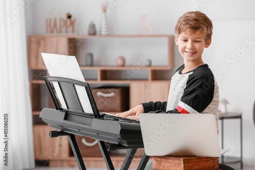 Fototapeta Little boy taking music lessons online at home obraz