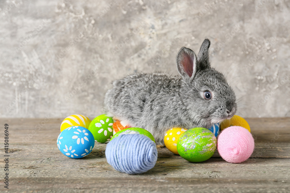 Fototapeta Cute rabbit and Easter eggs on table against grey background