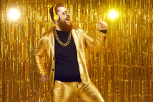 Happy Eccentric Redhead Man Wearing Crazy Suit, Gold Neck Chain And Stylish Wireless Headphones Enjoying Free Unlimited Online Music, Listening To Favorite Audio Track, Singing, Dancing And Having Fun
