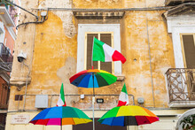 Italy, Apulia, Metropolitan City Of Bari, Bari. Rainbow-colored Umbrellas And An Italian Flag In Front Of An Old Building.