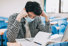 Stressed Young  Student Wearing Face Mask And Studying In  Classroom