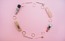 Round Frame Made Of Hair Clips With Pearls And Gold Rings On  Pastel Pink Background. Flat Lay. Top View.