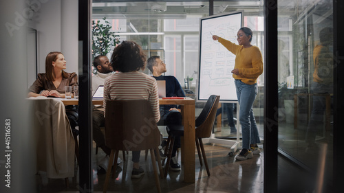 Project Manager Makes a Presentation for a Young Diverse Creative Team in Meeting Room in an Agency Fototapeta