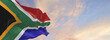 canvas print picture - Large flag of South Africa  waving in the wind on flagpole against the sky with clouds on sunny day. 3d illustration