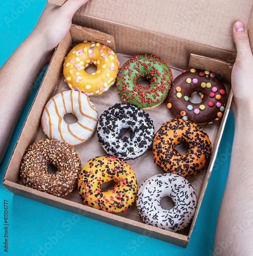 hand holds a box of doughnuts with different flavors