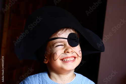 A happy young boy wearing a pirate costume. black background. Fototapeta