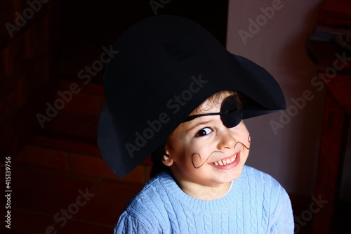 Fotografia A happy young boy wearing a pirate costume. black background.