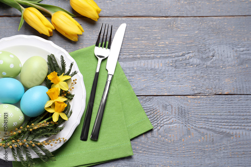 Festive Easter table setting with eggs on grey wooden background, flat lay. Space for text