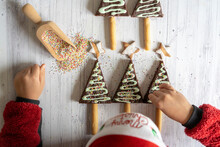 Overhead View Of Little Child With Santa Hat Decorating The Home Made Chocolate Brownies And Cookies In Shape Of Christmas Tree