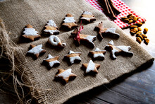 Gingerbread And Butter Cookies In Shape Of Christmas Tree, Stars And Reindeer On Canvas Place Mat On Wood Table Background