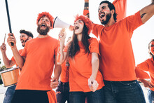 Orange Sport Fans Screaming While Supporting Their Team Out Of The Stadium - Football Supporters Having Fun At Competion Event - Focus On Center Girl Face