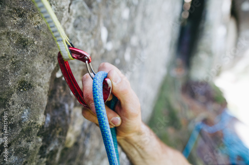 Photo Close up of rock climber hand clipping rope in a quick draw caribener on a cliff