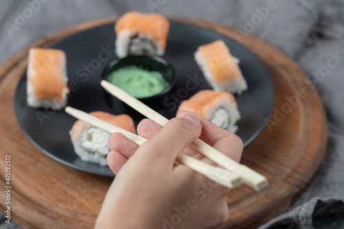 Canvas Print Salmon rolls with cream cheese in a black plate with wasabi sauce