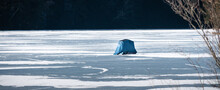A Blue Ice Fishing Sled With Shelter Is On The Frozen Lake In  Nathaniel Cole Park In Harpursville In Broome County In Upstate NY.  Look Closely And You Can See The Feet Of The Fisherman Inside.
