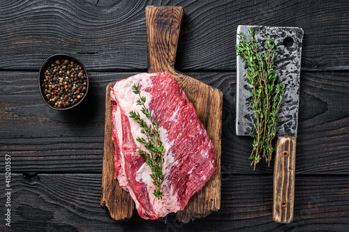 Fresh Raw Round roast beef meat cut on a butcher cutting board with cleaver. Black wooden background. Top view