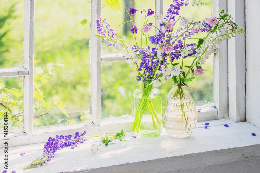 Fototapeta summer flowers in vase on windowsill in sunlight