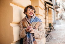 Pretty Woman In Glasses Posing In Cold Day. Outdoor Shot Of Smiling Girl In Coat Using Smartphone.