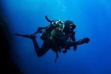 Scuba Diver Swimming In Deep Blue