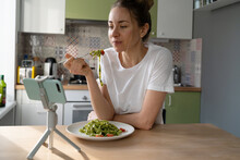 Woman Eating Slowly Pasta With Vegetarian Pesto Sauce, Watching Movie On Smart Phone On Tripod At Home Kitchen. Italian Cuisine, Gluten Free Food. Slow Living.